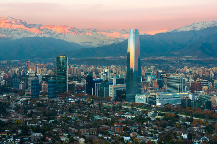 Panoramic view of Providencia and Las Condes districts with The Andes Mountain Range at sunset, Santiago de Chile Andes Architecture Chilean  City Cityscape Financial District  Las Condes Pedro De Valdivia Norte Providencia Sanhattan Santiago De Chile Skyline Sunlight The Andes Mountain Range Buildings District Dusk Mountain Range Mountains Neighborhood Skyscraper Snow Capped Sunset