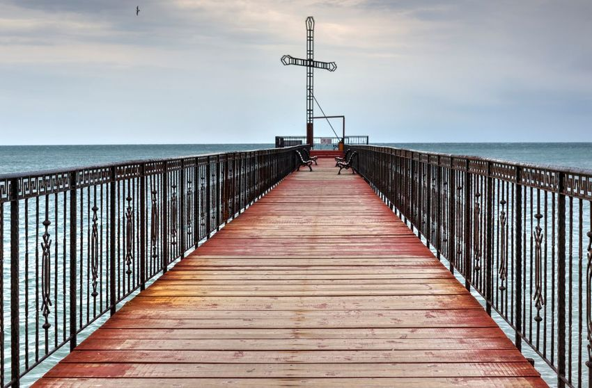 Sea And Sky Cross Cristian Pier Showcase: February Religion Benches Blue Sky Blue Sea Black Sea Railing Expectation Metal Structure Hope Benches Summer Day Outdoors No People The Way Forward Tranquil Scene