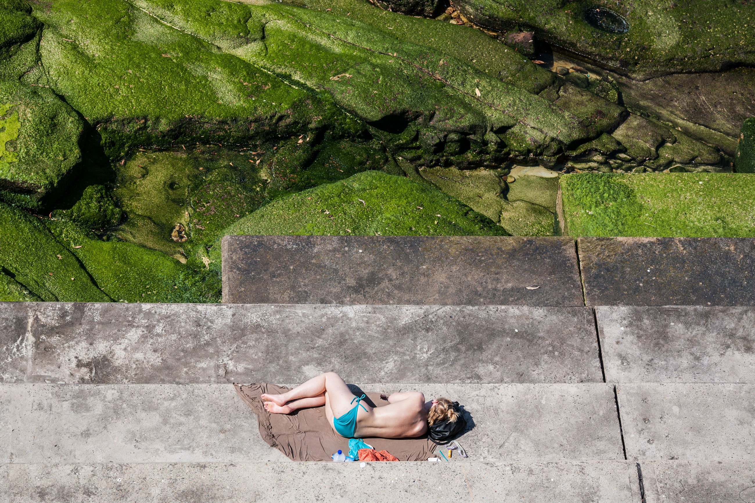 high angle view, one person, day, outdoors, young adult, full length, leisure activity, one woman only, one young woman only, young women, lifestyles, only women, lying down, water, relaxation, women, adults only, beautiful woman, adult, people