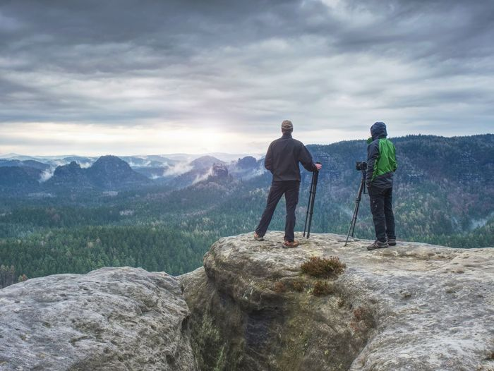 Tourist couple on the top of rocky mountain. friends in nature.