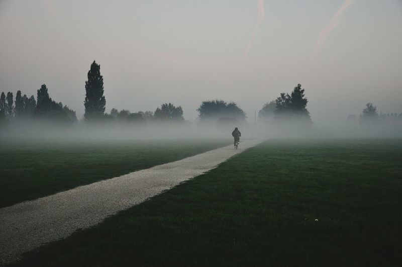 Person riding bicycle on footpath against sky during foggy weather