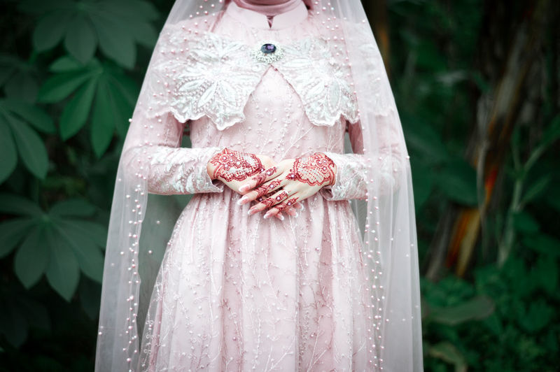 Close-up of woman standing by pink dress