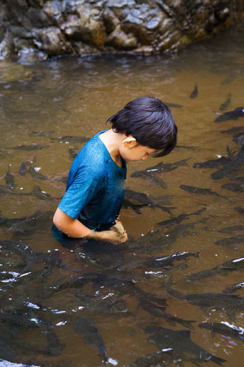 High angle view of boy in standing in lake water
