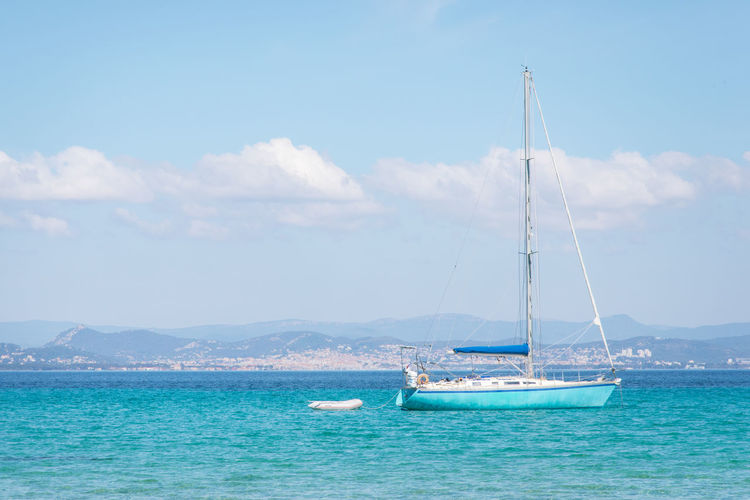 Boat Nautical Vessel Sea Sky Transportation Water Sailboat Mode Of Transportation Cloud - Sky Sailing Nature Day Scenics - Nature Travel Pole Waterfront Beauty In Nature Mast Blue Yacht No People Outdoors Yachting Turquoise Colored Luxury Travel Destinations Tourism Calm Sailing Boat Water Vehicle