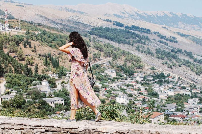 Woman on wall against mountain landscape