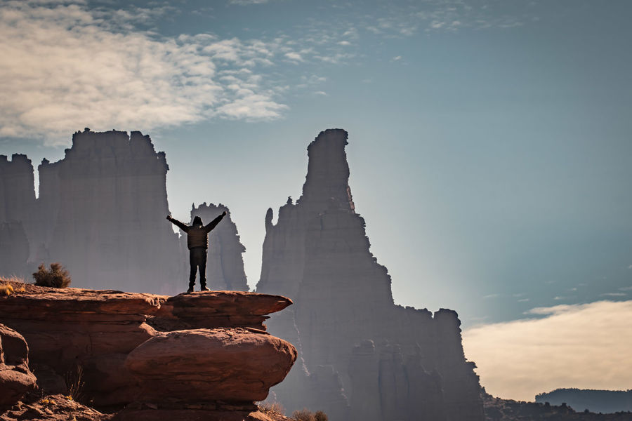 Man standing on rock outcropping with hands raised looking out to desert scene Beauty In Nature Cloud - Sky Day Desert Landscape Fisher Towers Full Length Leisure Activity Man On Rocks Moab Utah Mountain Nature One Person Outdoors People Real People Rewilding Rock - Object Scenics Sculpture Sky Statue Tranquility Travel Destinations Go Higher #FREIHEITBERLIN The Great Outdoors - 2018 EyeEm Awards