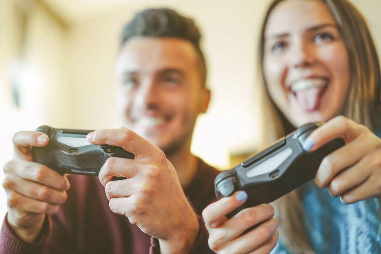 Smiling couple playing video game at home