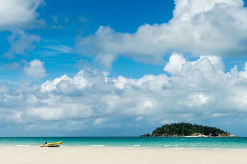 A small dingy sits on the white sand beach of Whitsunday Island, Australia. Australia Beach Beauty In Nature Blue Boat Calm Cloud Cloud - Sky Cloudy Day Horizon Over Water Island Nature Nautical Vessel Ocean Outdoors Scenics Sea Shore Tranquility Transportation Vacations Water Waterfront