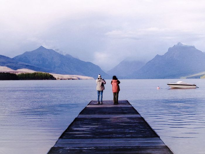 Rear View Of Two Tourists On Jetty In Winter