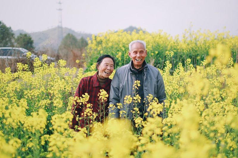 Smiling Couple Standing Amidst Flowering Yellow Plants