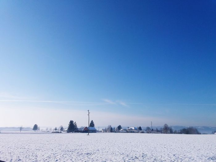 Scenic view of snowy field against clear blue sky