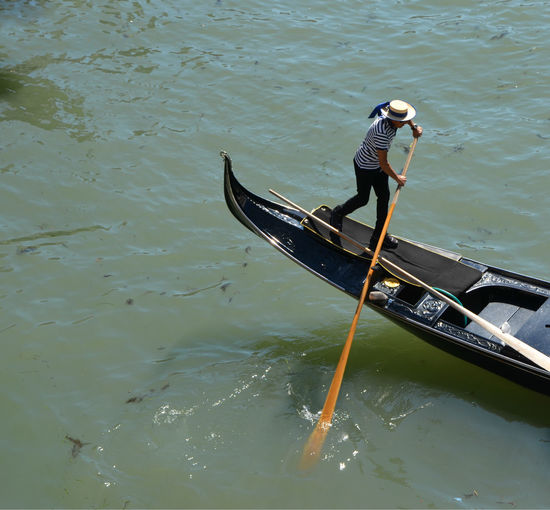 High Angle View Of Gondolier Rowing Gondola In Canal