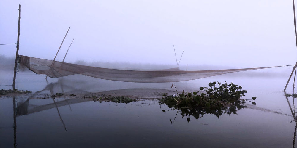 Fishing nets over a foggy river Fishing Net Foggy Morning Backwaters Tranquility Nature Photography Reflections In The Water