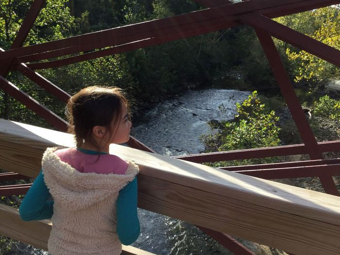 One Person Leisure Activity Tree Railing Nature Standing Day Plant Casual Clothing Wood - Material Architecture Waist Up Outdoors Rear View Built Structure Girl Real Person River Bridge Iron Bridge Historic Structure Railroad Track
