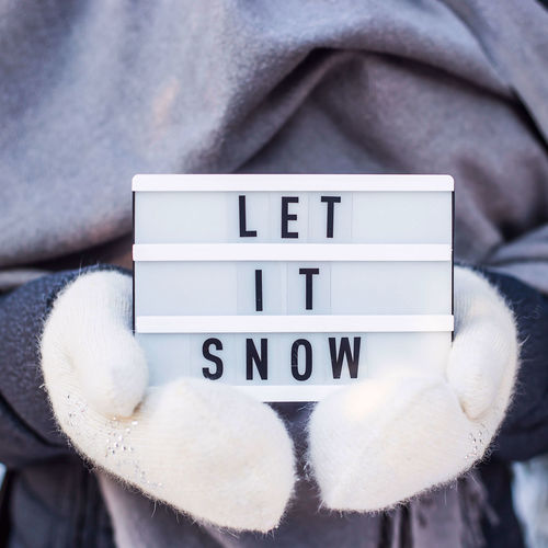 Let it snow it is written on a decorative lamp in the hand of a woman in a white mitten against the background of green spruce branches covered with snow Close-up Communication Text Let It Snow Snow Winter Christmas New Year christmas tree Decoration Lamp Text Letters Phrase Saying Hold Females Woman White Mitten Cold Weather