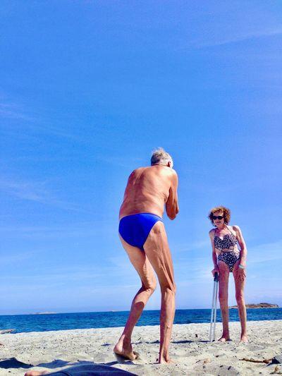 Full length of friends on beach against clear blue sky