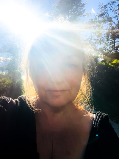 Portrait of woman against bright sun on sunny day