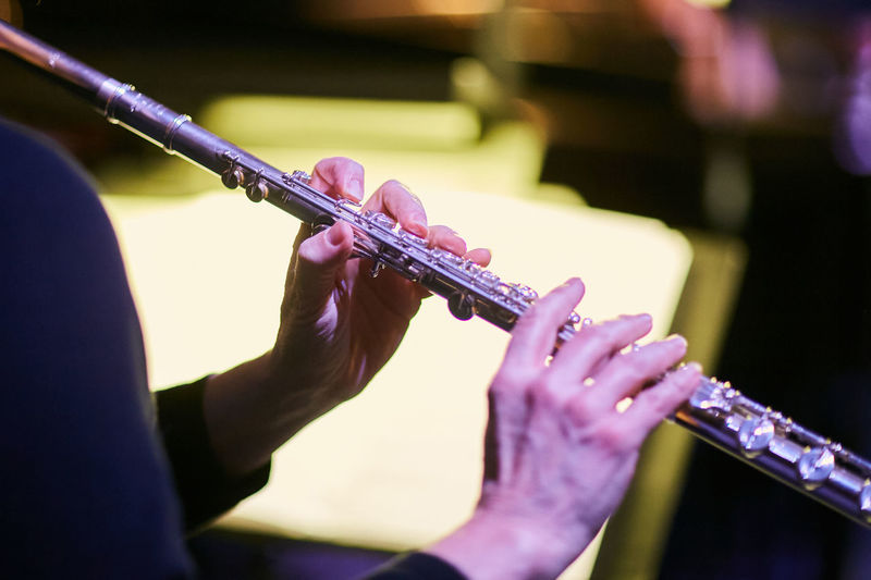 Cropped hands of musician playing flute