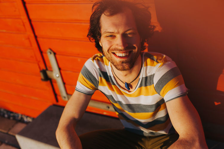 portrait of cheerful caucasian man smiling Joyful Laughing Sitting Beard Casual Clothing Cheerful Emotion Facial Hair Focus On Foreground Front View Happiness Indoors  Joy Leisure Activity Lifestyles One Person Portrait Real People Sitting Smile Smiling Sunset Three Quarter Length Young Adult Young Men