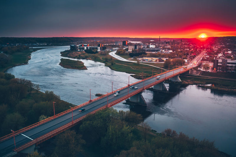 Aerial view of bridge over river in city against sky