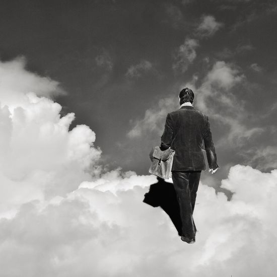 Digitally generated image of man walking on clouds in sky