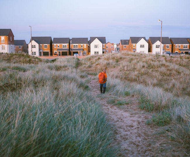 Rear view of man walking on field by houses against sky