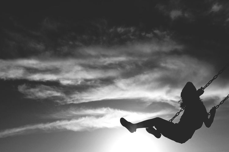 Low Angle View Of Silhouette Girl Swinging On Swing Against Sky