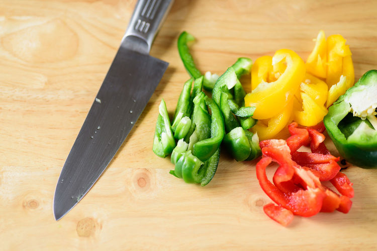 Sliced green, yellow and red bell peppers with knife on wooden background, food ingredient Bell Pepper Bright Capsicum Chop Chopped Colorful Cooking Cuisine Cutting Food Fresh Freshness Gourmet Green Health Healthy Ingredient Knife Nature Nutrition Organic Paprika Pepper Recipe Red Ripe Sliced Sweet Vegetable Vegetarian Wood Wooden Yellow Healthy Eating Wellbeing Kitchen Knife Cutting Board Table Still Life Indoors  High Angle View Preparation  Table Knife