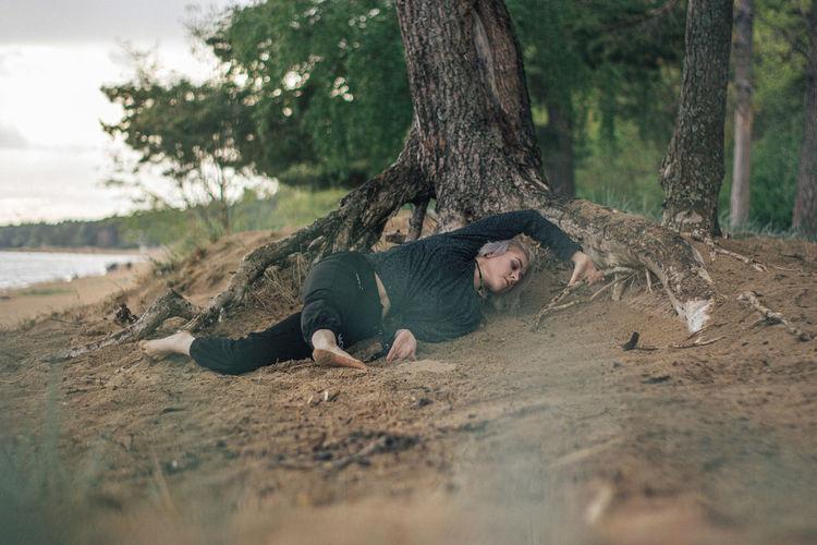 Full length of man lying on tree trunk
