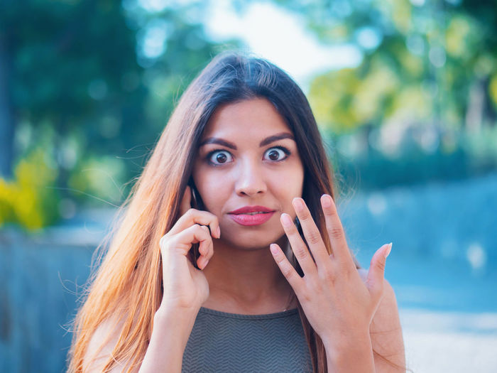 Portrait of shocked woman talking on mobile phone