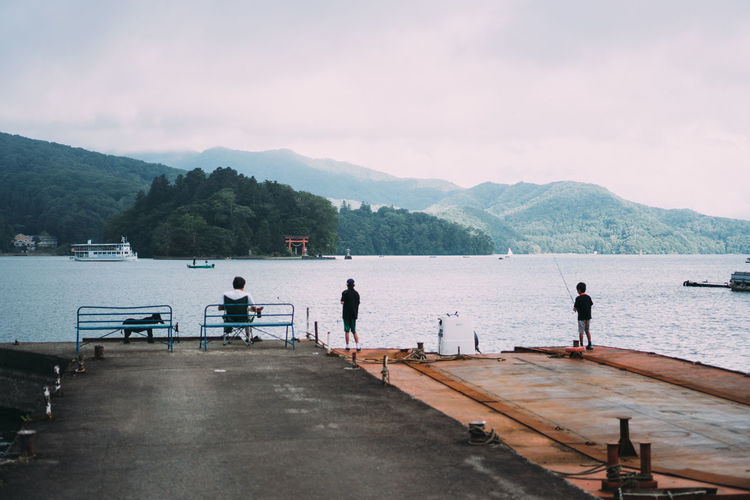 People on pier over sea against mountains and sky