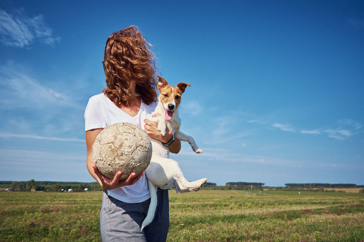 Woman holding dog with ball on field against sky