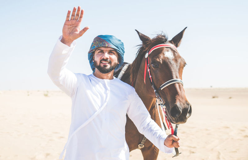 Portrait of man with horse walking at desert against clear sky