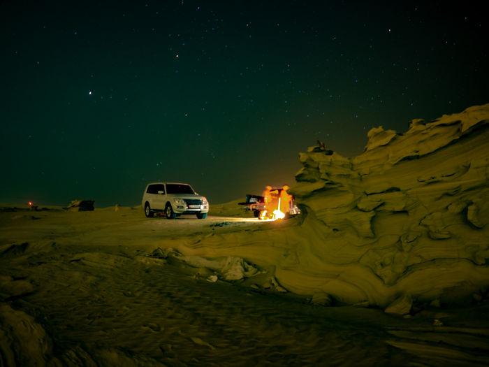 Cars on illuminated land against sky at night