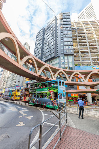 Hong Kong, China - December 6, 2016: people standing at the traffic lights under elevated skywalk between Pennington Street and Yee Wo Street in the famous luxury shopping district of Causeway Bay. Hong Kong City Sky Skyscraper Sky And Clouds Glass - Material Island Buildings Causeway Bay, Skywalk Bridge Architecture Built Structure Building Exterior Street Day Building Transportation City Life Road Real People Men Nature People Incidental People Cloud - Sky Footpath Lifestyles Outdoors Office Building Exterior Modern