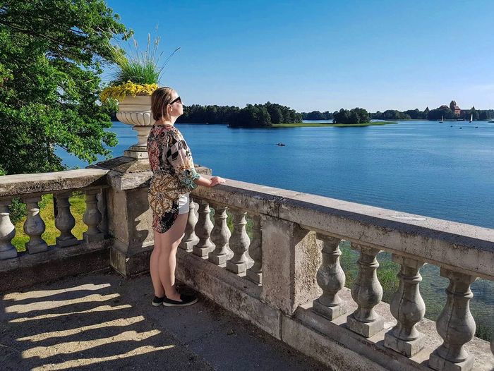Enjoying hot summer day Woman Plant Water Tree Day Nature Sunlight Sky Clear Sky Railing Architecture Representation Beauty In Nature Tranquility Growth Built Structure Outdoors Lake Tranquil Scene