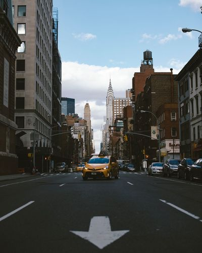 Yellow Taxi On City Street With Chrysler Building In Background