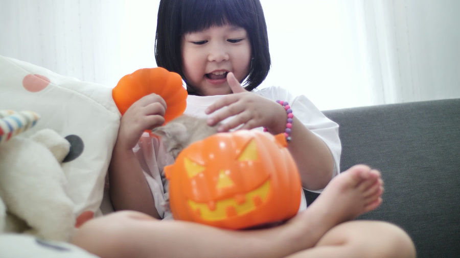 Cute Girl With Kitten In Jack O Lantern At Home