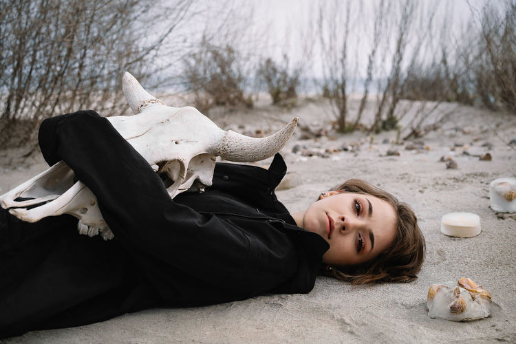 Portrait of young woman lying down on the beach