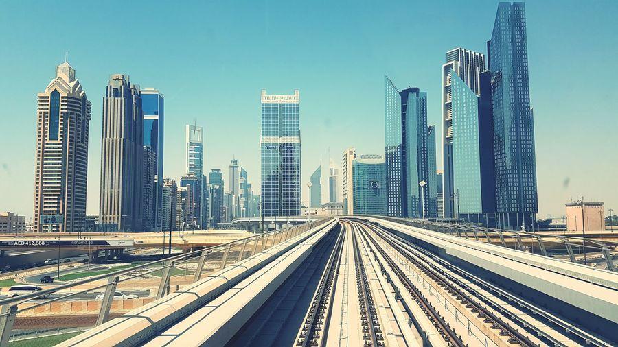 Railroad tracks against modern buildings in city