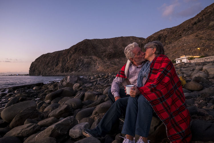 Couple Kissing While Sitting On Rocks Against Sky At Beach