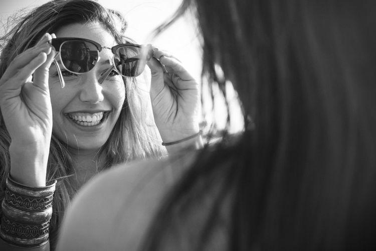 Close-Up Of Female Friends Holding Sunglasses