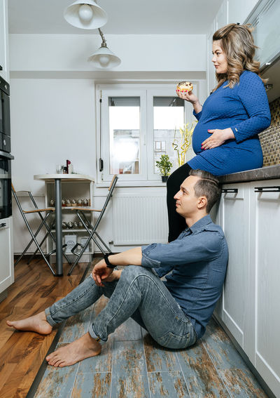 Watching TV. Pregnant Pregnancy One Man Only One Woman Only 2 People Couple Woman Man People Real People Couple - Relationship Togetherness Sitting Full Length Domestic Life Women Home Interior Domestic Room Men Family Bonds Two Parents Posing Personal Perspective