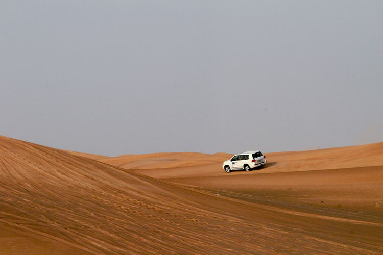 View of car in desert against clear sky