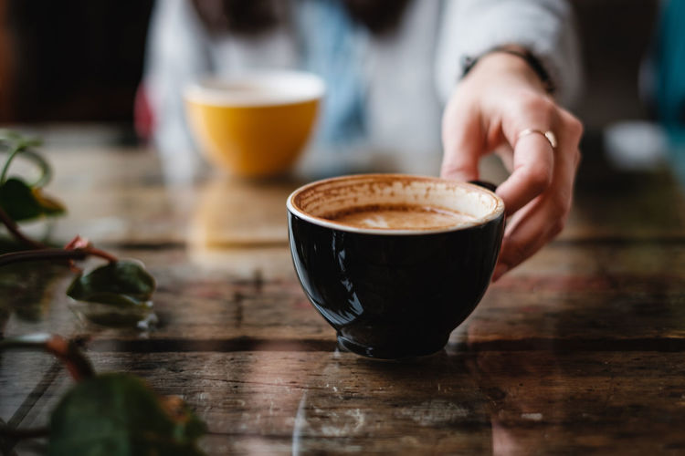 female hand taken cup with coffee in the cafe Drink Food And Drink Coffee - Drink Coffee One Person Coffee Cup Wood - Material Holding Frothy Drink Baristalife Barista Latteart Selective Focus Cafe Human Hand Drinking Glass Latte Freshness Table Mug Cup Refreshment Hot Drink Arabic
