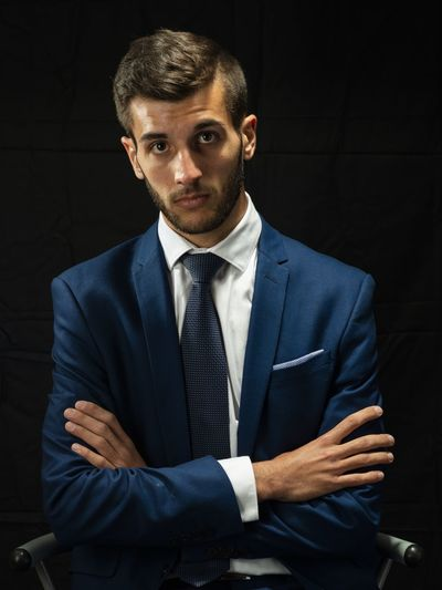 Portrait of young man in suit sitting against black background