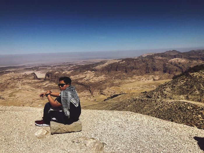 Full length of man sitting on rock against landscape