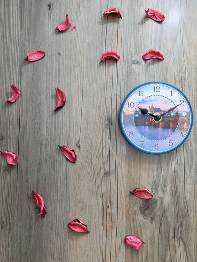 Close-Up Of Clock And Petals On Table