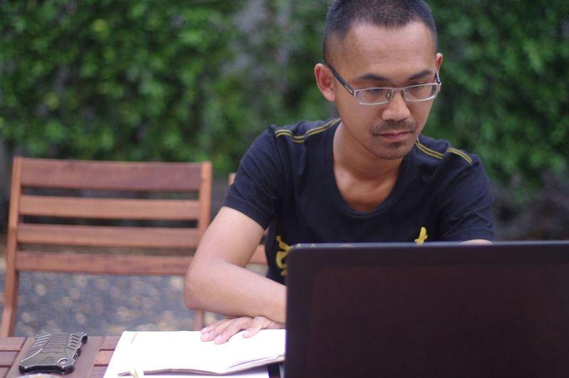 Man using laptop while sitting outdoors