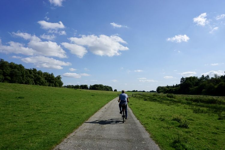 Rear view of person walking on road amidst field against sky